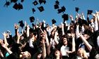 A group of Aberystwyth university students graduating on graduation day, throwing their caps in air
